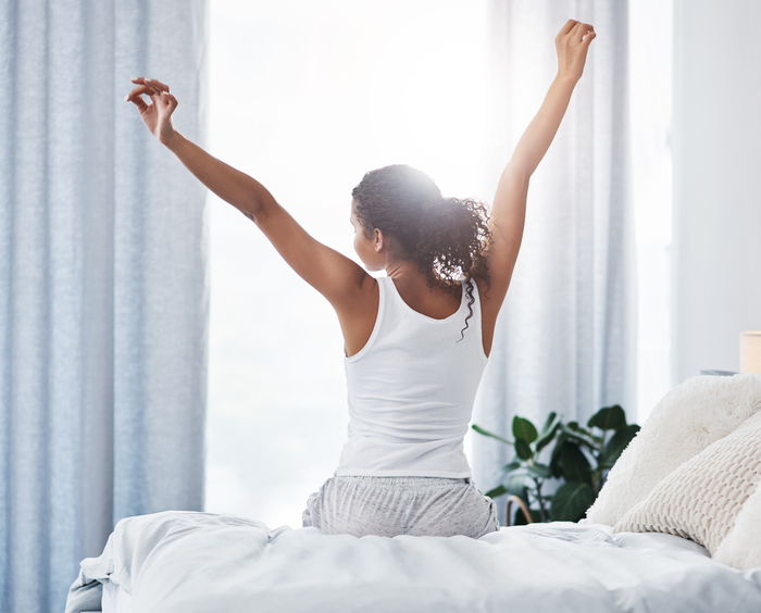 Woman waking up in bed and stretching