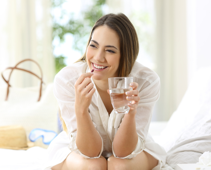 Woman taking capsules with a glass of water